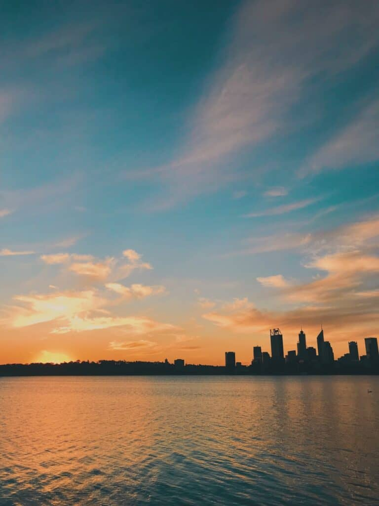 silhouette of city buildings near body of water during sunset